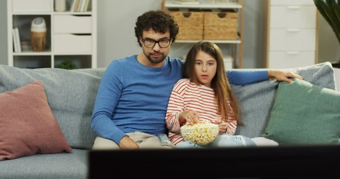 c06208739d Caucasian father and his small pretty daughter sitting on the couch with  popcorn and watching horror
