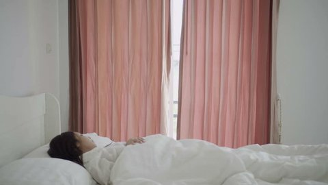 Happy asian woman waking up and open curtains at morning with sunlight shine through window. Beautiful young girl in casual have a good day looking away while standing at window in bedroom at weekend