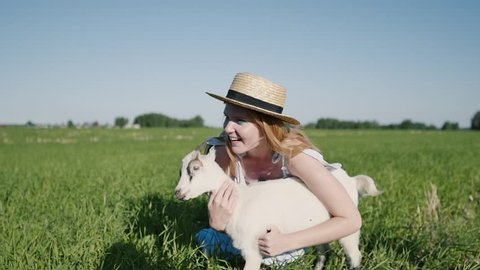 Happy young girl caressing happy cute kid goat on smallholding farm. Beautiful domestic animal enjoying warm sunny summer day