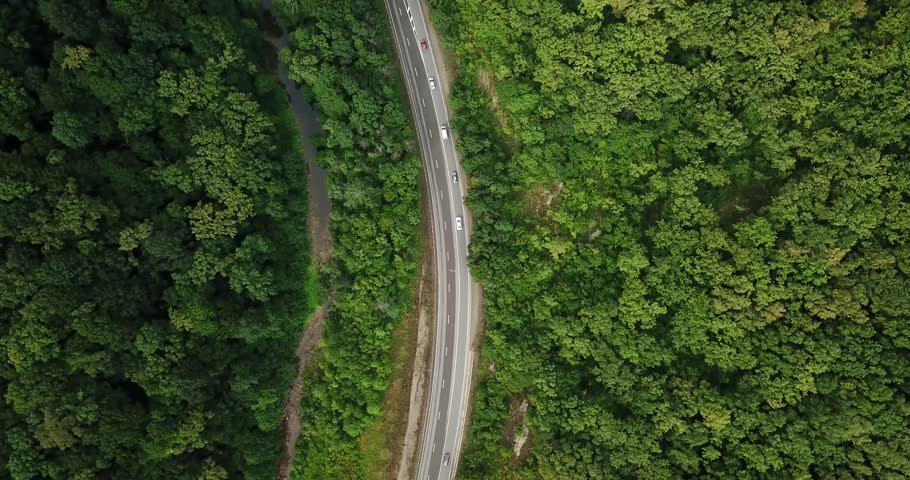 4K aerial stock footage of car driving along the winding mountain pass road through the forest in Sochi, Russia. People traveling, road trip on curvy road through beautiful countryside scenery. #1013943566