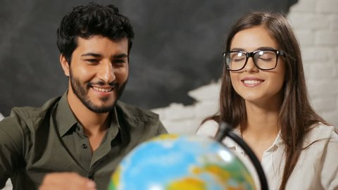 Happy family couple choosing travel destination, thrilled husband turning big globe when dreaming wife with closed eyes points at the country to visit, indoor shot in travel agency