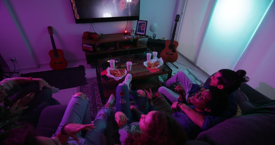 Young multi-ethnic friends hanging out at home, eating fast food and watching film on TV
