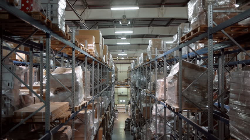 A large warehouse with boxes of goods. The camera moves up along the shelves with cardboard boxes. A forklift works in the distance | Shutterstock HD Video #1013993906