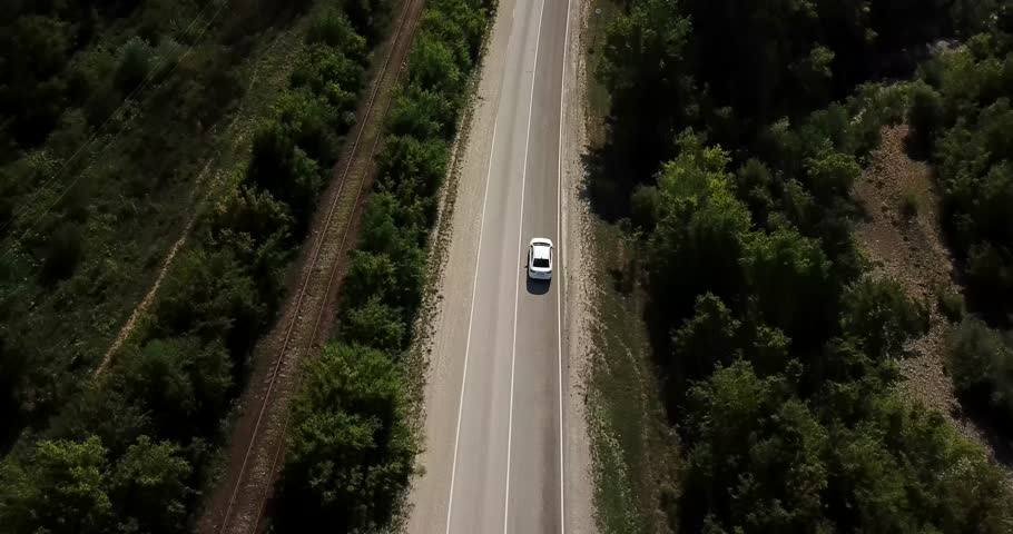 Aerial view flying over old patched two lane forest road with cars van moving green trees of dense woods growing both sides - shot with drone quad copter birds eye view perspective from above #1013998196
