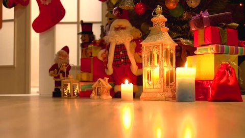 Burning candles and Christmas decorations. Lantern with a burning candle, Santa Claus toy, gift boxes and Christmas tree. Christmas holiday traditions.