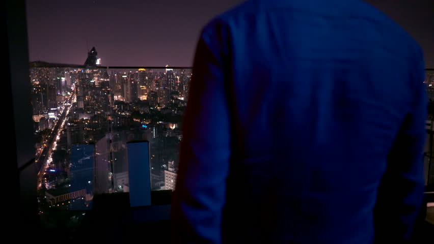 Young man admiring view from terrace during night, 4K. | Shutterstock HD Video #1014008306