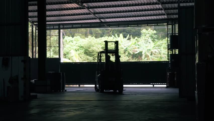 Fork-Lift Entering A Factory Warehouse From The Left - Silhouette