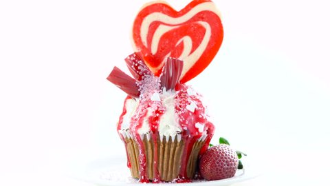Red and white theme colorful novelty cupcake decorated with candy and large heart shaped lollipop for Valentine's, Mother's Day and birthday celebration.