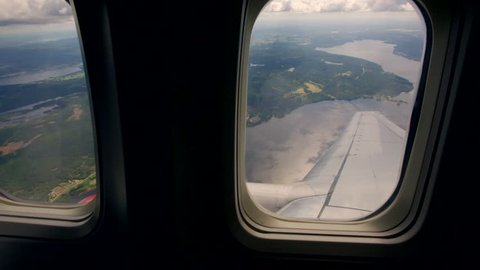 A view through the windows of an airplane in flight on approach to Oslo airport.