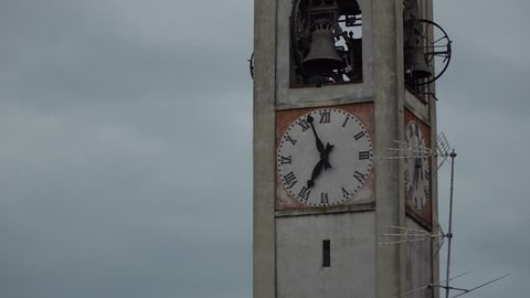 Clock tower with clock-face and bell in old Italy city, bad weather