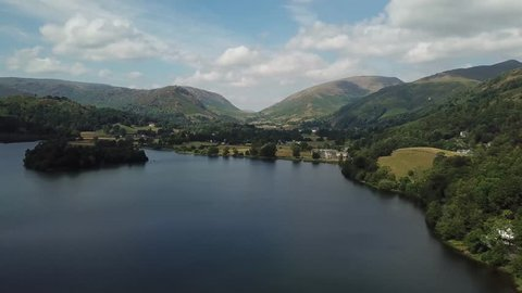Aerial shot over a lake with blue skies and mountains | The Lake District | 4K