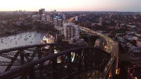 Aerial drone footage flying on the left side of the harbour bridge in warm afternoon sunlight with water and Sydney city horizon in the background