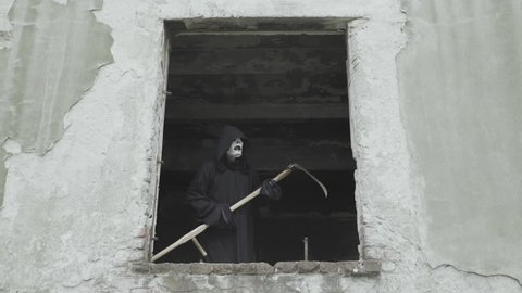 Grim reaper with mower comes out on window hole of destroyed building. Black demon of death looks at camera and then returnes back in the darkness, evil from hell, symbolic horror scene, soul harvest.