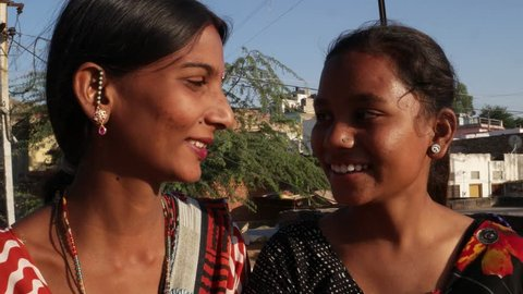 Handheld extreme closeup of two beautiful sweet pretty female  friends bonding pov of selfie stick with smart phone on  the terrace of their house in rural India smiling and laughing as they pose