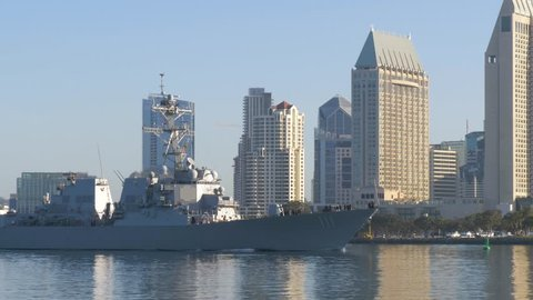 Warship sails against the background of San Diego's downtown in the morning at dawn.