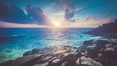 Beautiful tropical sunset view from the rocky coast of Thailand. Nature landscape. Holidays, travel, vacation. Water waves movement and clouds in sky float. Zooming. 4K Slow Motion Time Lapse Parallax
