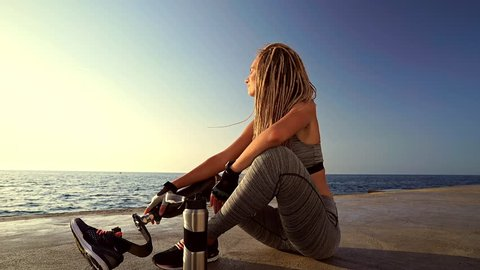 Side view of Young Tired disabled athlete woman with prosthetic leg relaxing after run at the beach