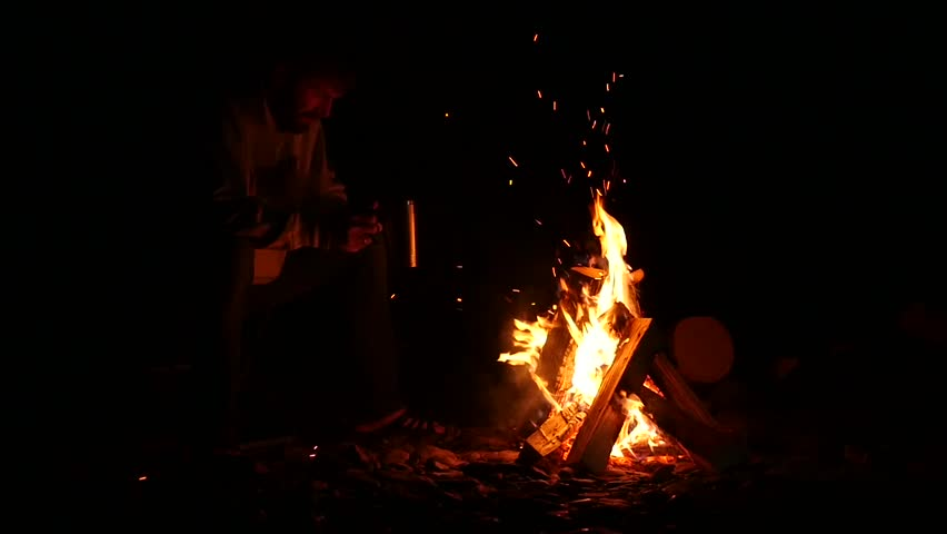 Bearded men drink tea from big cup and make a photo on a cellphone of bonfire in a dark. slow motion | Shutterstock HD Video #1014148916