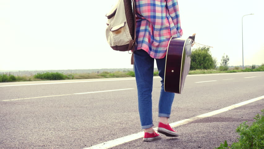 Young girl with a guitar coming along the road and hitch-hiking