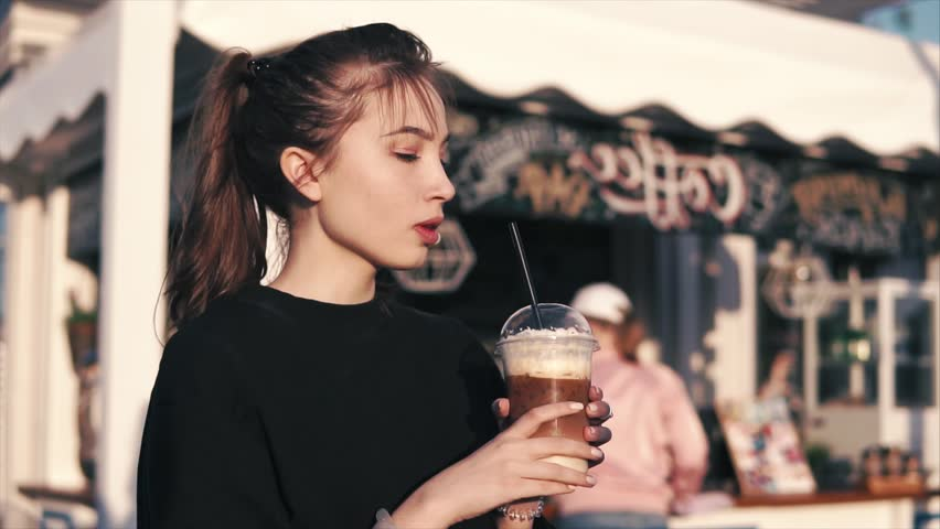 Portrait of a young woman drinking sweet and fresh coffee cocktail outdoor. #1014185036