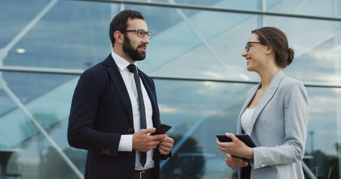 Good looking man in business style and smartphone in hands speaking and making compliments to a pretty woman in office style.