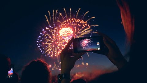 A woman captures fireworks on video, close up.