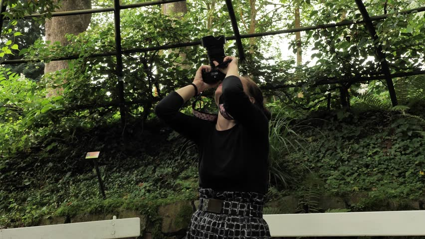 4k beautiful girl in black handmade dress standing inside of oval summer garden metal arbor construction shooting photo with dsl premium objetive in slow motion round moving motion camera #1014215516