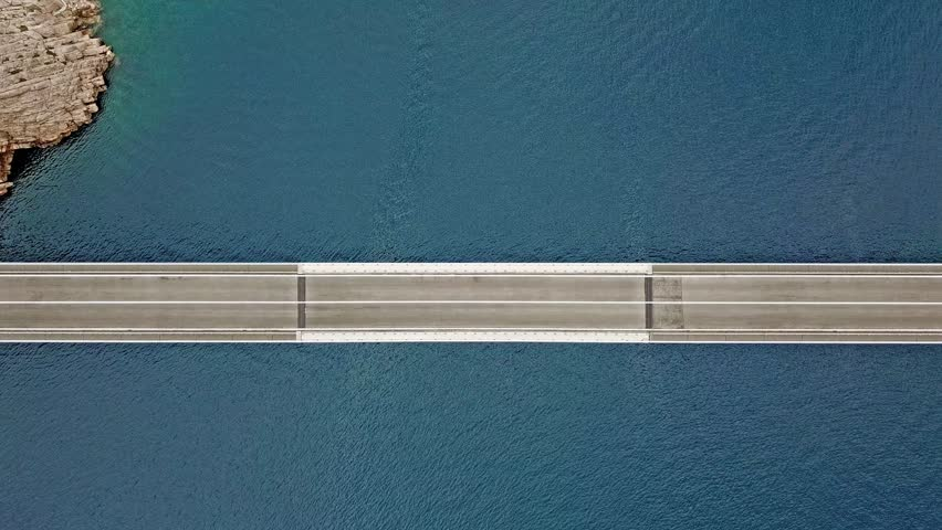 Aerial view of the bridge of the island of Pag, Croatia, road. Cliff overlooking the sea. Cars crossing the bridge seen from above
