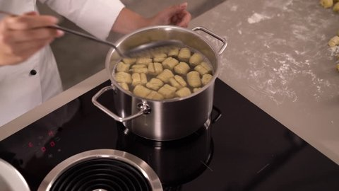 4K cooking footage, close up female cook lifting fresh gnocchis out of hot water in pot placing gnocchi on plate with tomatoes