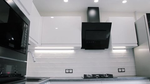 interior of white modern compact kitchen. suspended ceiling with LED lamps.