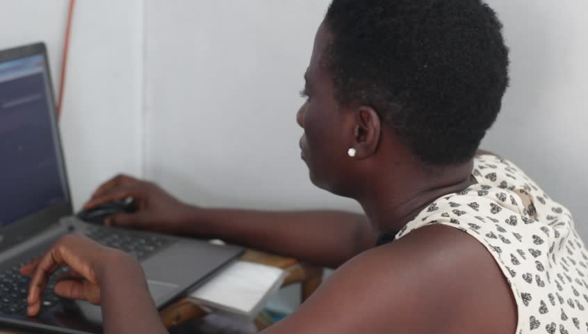 Young woman is working on laptop with great concentration.