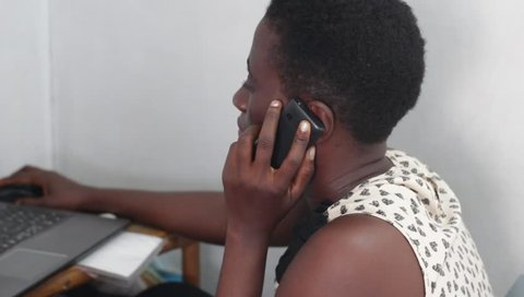 Young woman is working on a laptop while phoning