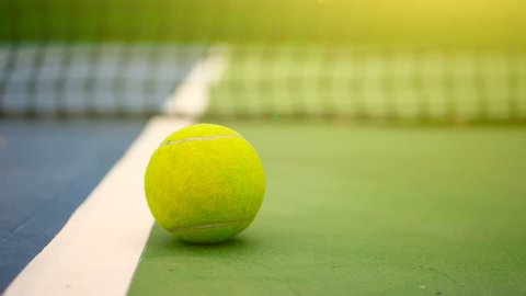 Close up of tennis equipment on the court. Sport, recreation concept. Yellow tennis balls in motion on a clay green blue court next to the white line with copy space, soft focus and net in background.