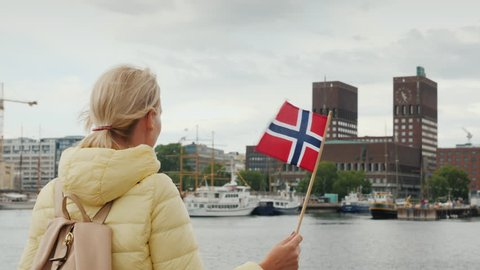 A female tourist with a flag of Norway is standing on the pier, looking forward to the city of Oslo, the capital of Norway. A Journey Through Scandinavia Concept