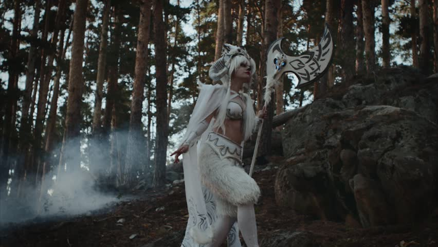 Model dressed like mythical faun is strolling in forest near spruces. She is carrying hatchet in hands, tilt up view #1014321116