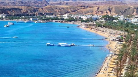 The comfortable sand beach line of El Maya bay, surrounded by red rocky mountains, Sharm El Sheikh, Egypt.