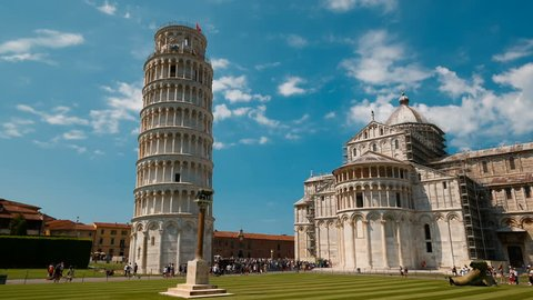 Wide tracking shot of the Leaning Tower of Pisa and Pisa Cathedral in Piazza dei Miracoli, Italy, featuring the famous bell tower. Pisa has more than 20 historic churches and several medieval palaces
