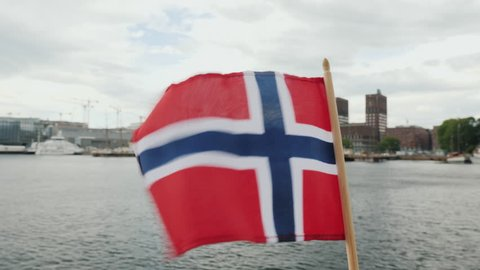 Walking with the flag of Norway against the background of the city line of Oslo