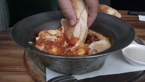 Dipping Bread into Shakshuka Poached Eggs with Tomato Served in a Frying Pan. Israeli Arab Middle Eastern Cuisine