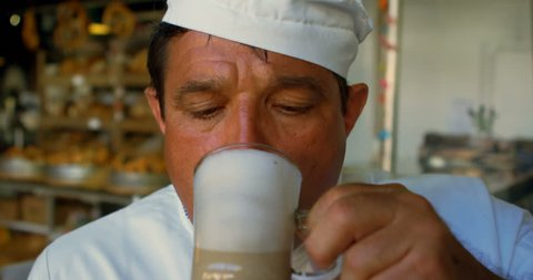 Close-up of chef drinking chocolate milkshake in commercial kitchen 4k