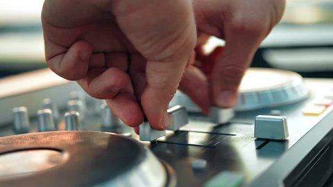 Male hands of Disk Jockey mixing music tracks tweak various controls on deck