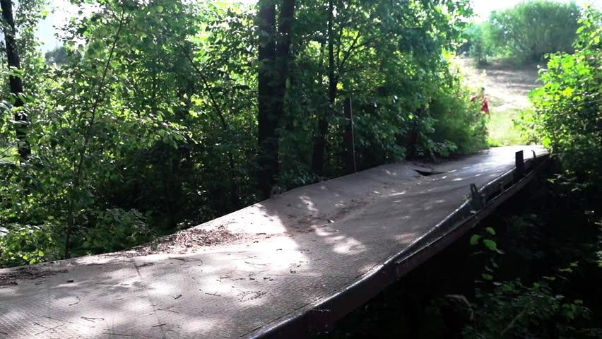 A woman is walking along a broken bridge in the forest