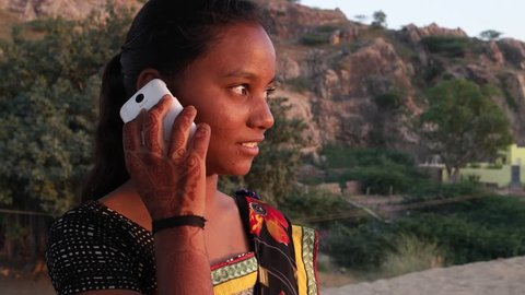 Teenage girl dials talks idea smart mobile phone looking around outdoor nature hill top smile happy joy fun panoramic view viewpoint sunset dusk on a hot summer day in India handheld stabilized sand
