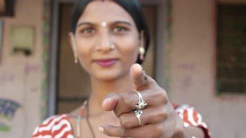 Close up of beautiful Indian lady in traditional dress looks and points at camera thumbs up best of luck be good finger leader command select face approves hand gesture smiles happy focus shift