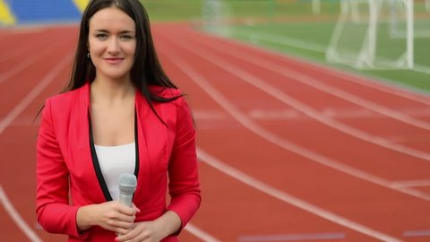 Woman with microphone makes reportage from running tracks