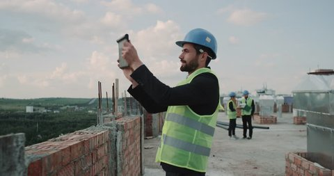 Architect make pictures on rooftop of building background builders analyzing the plan of construction site. 4k