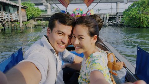 Asian tourist couple having an intimate real selfie moment, taking picture on tour longtail boat, on the chao phraya river water way in Bangkok, Thailand. Slow motion