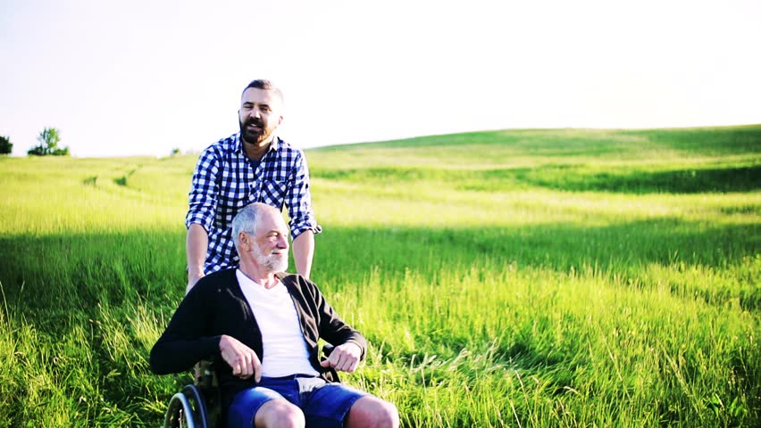 An adult hipster son with senior father in wheelchair on a walk in nature at sunset. #1014446666