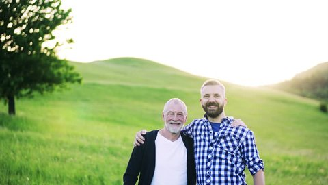 1377bdcc19 A portrait of an adult hipster son with senior father in nature at sunset,  arms