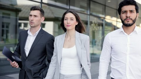 Close up view of Attractive Young Business People Exiting Office Building. Walking Together During Break. Wearing Classical Suits. Businessmen Holding Digital Devices in the Hands.
